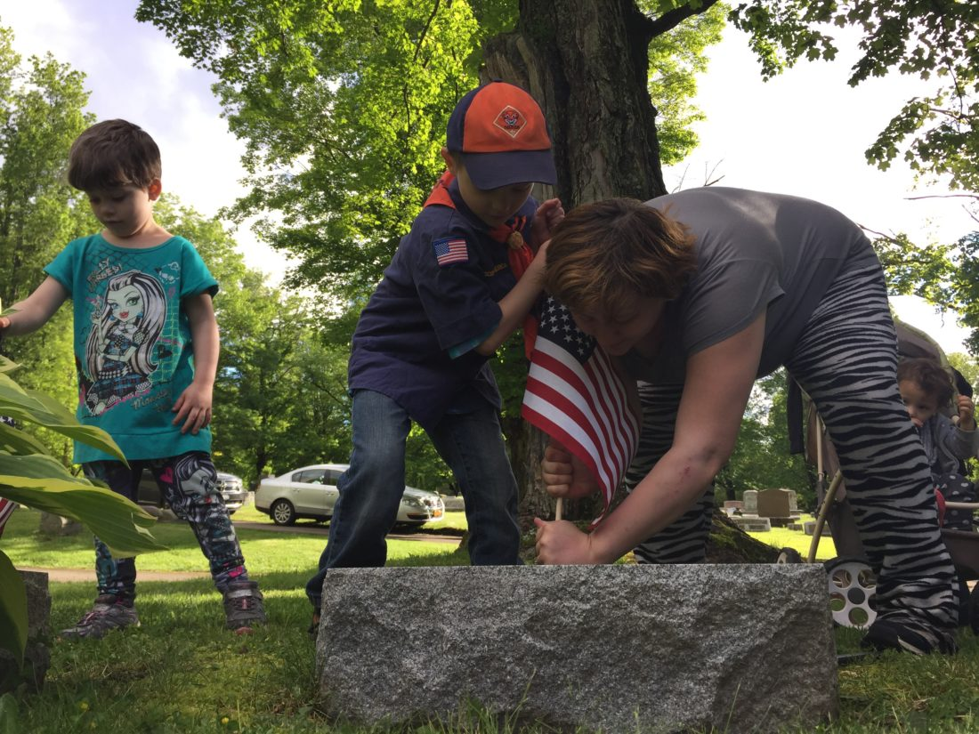 Phoenix Goodwill tries his best to plant a flag Thursday evening at Lakeview Cemetery in Jamestown with his sister, Majestic, at left.