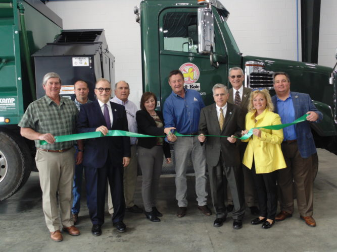 County and city officials visited Suit-Kote on Friday to get a glimpse of a new $937,000 warehouse facility. Frank Suits Jr., president, is pictured cutting a ribbon. P-J photo by Jimmy McCarthy