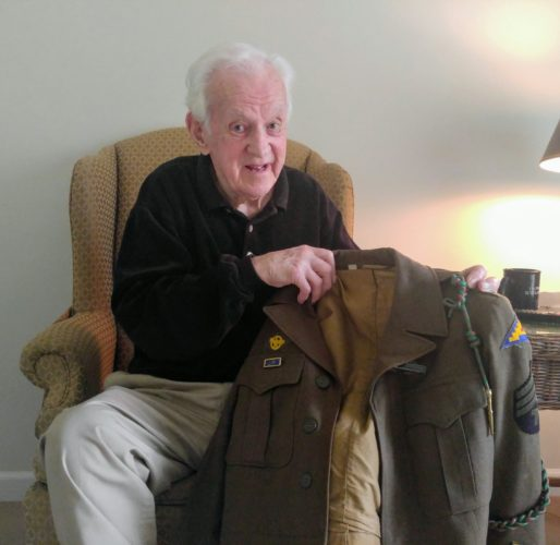 John Carter Rowland holds up one of his uniforms he wore during WWII.