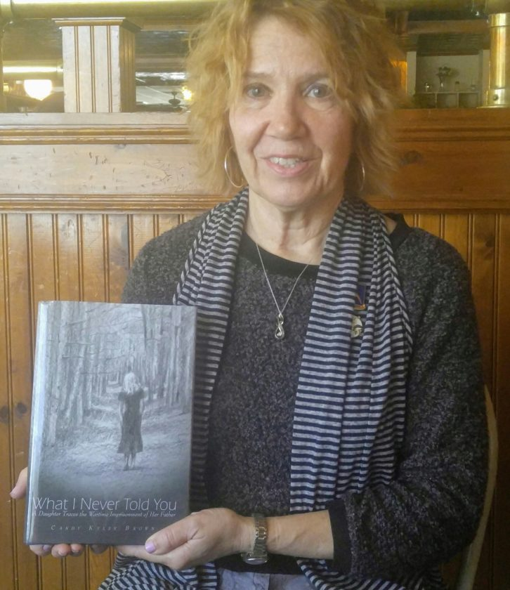 "Candy Kyler holds up a copy of her book ""What I Never Told You."" The story describes her father's wartime imprisonment."
