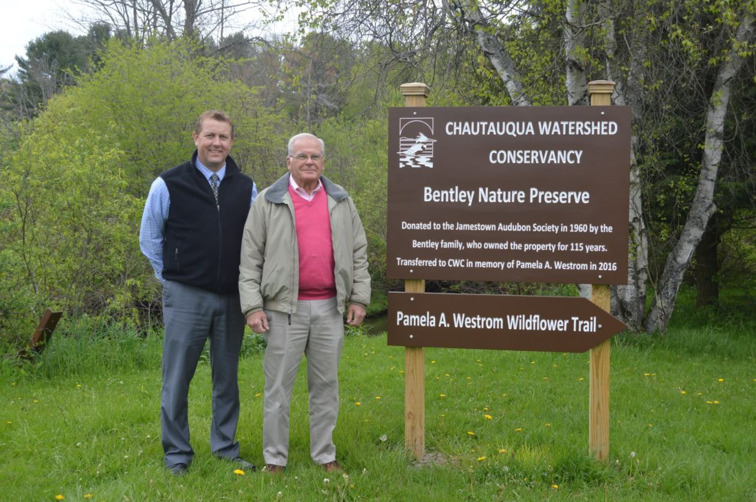 Doug Larson, Chautauqua Watershed Conservancy board president, and Curt Westrom stand at the entrance of the recently named Pamela A. Westrom Wildflower Trail. Submitted photo