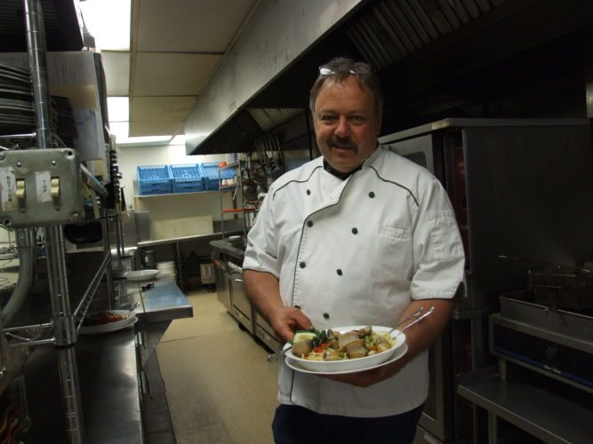 "Mike Seagren serves Clam Linguine in the kitchen, which he calls ""the center of gravity,"" at La Scala Restaurant."