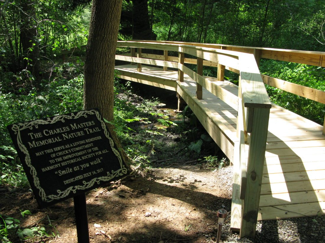 The Harmony Historical Society unveiled and dedicated a newly constructed angled wooden bridge at the site of the Charles Masters Memorial Nature Trail on its 1943 Open Meadows Road property in Ashville.