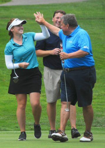 Above, pro Sara Banke, left, exchanges a high-five with Rich Dixon after the former rolled in a long putt for birdie on the 18th hole during the LINKS Charity at Moon Brook Country Club on Monday.  P-J photo by Scott Kindberg