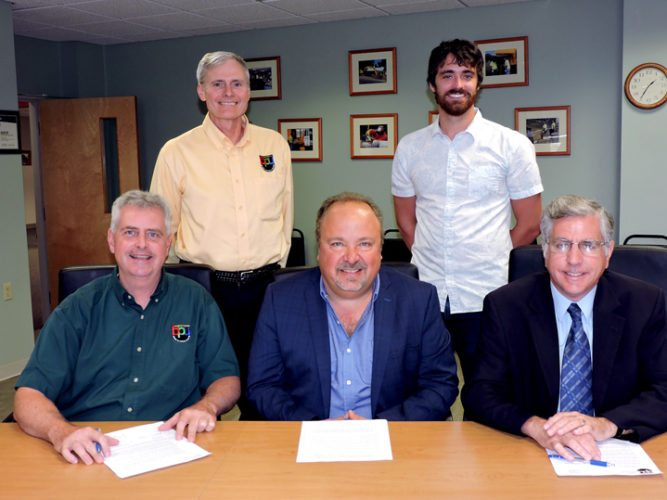 A flex-rate renewal agreement was signed by Monofrax President William Andrews, center, with Jamestown Board of Public Utilities General Manager David L. Leathers, left, and Jamestown City Mayor Sam Teresi, right. Looking on, back row from left, are BPU mechanical engineer David Gustafson and electrical engineer Kristofor Sellstrom. Submitted photo