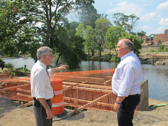 From left, Sam Teresi, Jamestown mayor, and Jeff Lehman, city public works director, discussing the pedestrian bridges that will be installed later this year over the Chadakoin River along the Greater Jamestown Riverwalk.  P-J photo by Dennis Phillips