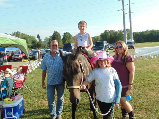 Horse rides were provided Wednesday at the Gerry Rodeo by MLW Stables of Russell, Pa. Pictured, from left, are Milton Wallace, owner, and volunteers Chase, Danielle and Samara.