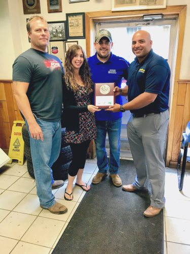 From left, Barmore Sellstrom Inc employees Chris Barmore, Samantha Clark, Aaron Liberati, and a Goodyear representative with the Goodyear Dealer Award for 25 consecutive years of loyal customership. Submitted photo