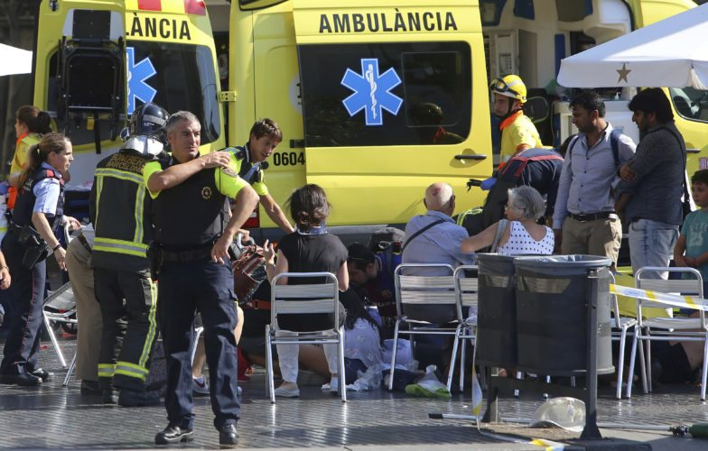 Injured people are treated in Barcelona, Spain, Thursday, after a white van jumped the sidewalk in the historic Las Ramblas district, crashing into a summer crowd of residents and tourists and injuring several people, police said.  AP photo