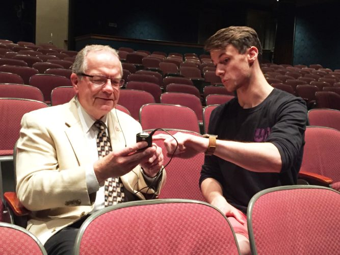 Stefan Duga, Reg Lenna Center for the Arts director of production and technology, demonstrates the updated hearing assistance system to Randy Sweeney, Chautauqua Region Community Foundation executive director. A grant from the Community Foundation's Fund for the Region purchased the equipment.