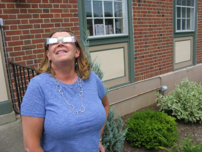 Katie Smith, Hazeltine Public Library director, poses with a pair of specialty sunglasses that were handed out to the public for Monday's partial solar eclipse. P-J photo by Eric Tichy