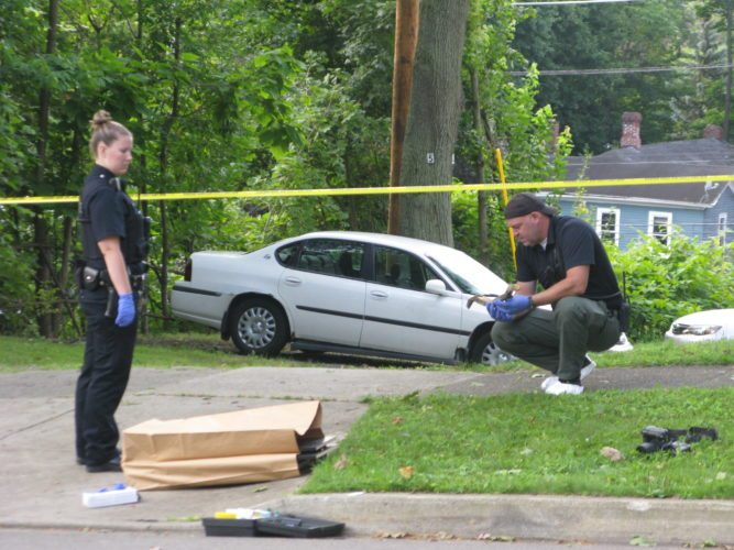 An investigator at East Sixth Street with an officer of the Jamestown Police Department.  P-J photo by Eric Tichy