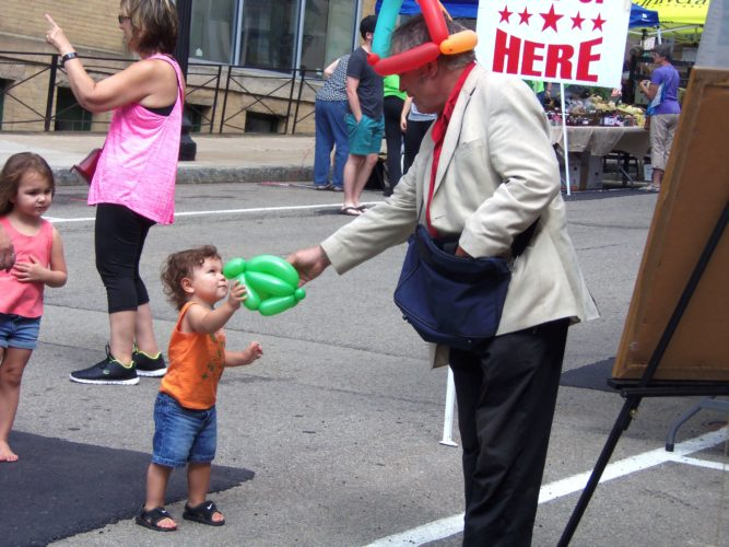 "Gary F. Mooney, also known as ""Mr. Balloon Man,"" hands a child a balloon animal at the Jamestown Public Market Community Day on Saturday.  P-J photo by Katrina Fuller"
