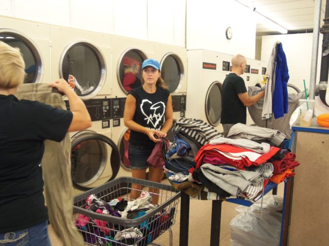 Conduit Ministries volunteers washed, dried and folded laundry for community members during the final day of the second annual I Am Loved Week at Papa Joes Laundromat in Jamestown on Saturday. P-J photos by Katrina Fuller
