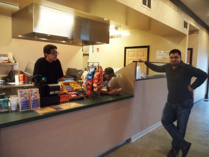 Holiday Inn Express general manager Maroun Kneiher, far right, spearheaded efforts to get the I-86 restaurant open again. Behind the counter are Jordan Wade, left, and restaurant manager Adam Thornton. P-J photo by David Prenatt