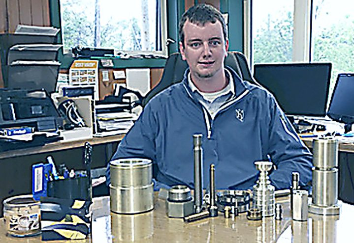 At only 24 years old, Andy Reinwald has been the owner of Ripley Machine & Tool Co. since 2015, and has worked for the company since he was a junior in high school. He sits in his office with some of the metal parts cut and ground inside the plant, at 9825 E. Main Road. P-J photo by Charles Erickson