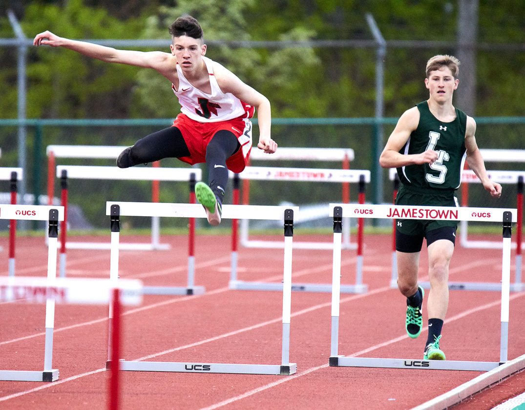 JHS Red Raider, Andrew Dix, cleared a hurdle during a track meet.  Photo by Chad Ecklof Photo Art