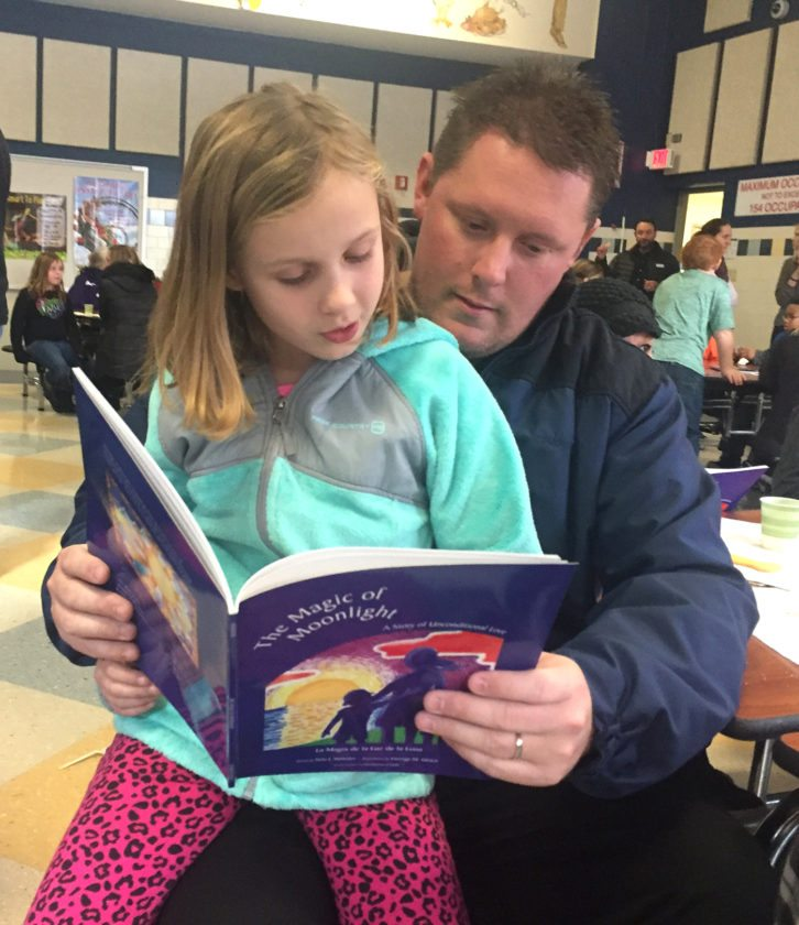 "Lincoln Elementary School student, Abigail Brandow and her dad, Mike, read Nila Webster's book ""The Magic of Moonlight"" as part of a family engagement event. Mrs. Webster donated books to every first grader in the Jamestown Schools to take home. Lincoln School used the donation to also ask families for ""wish list"" items for the Chautauqua County Humane Society in honor of the main character in the book, which is a dog."