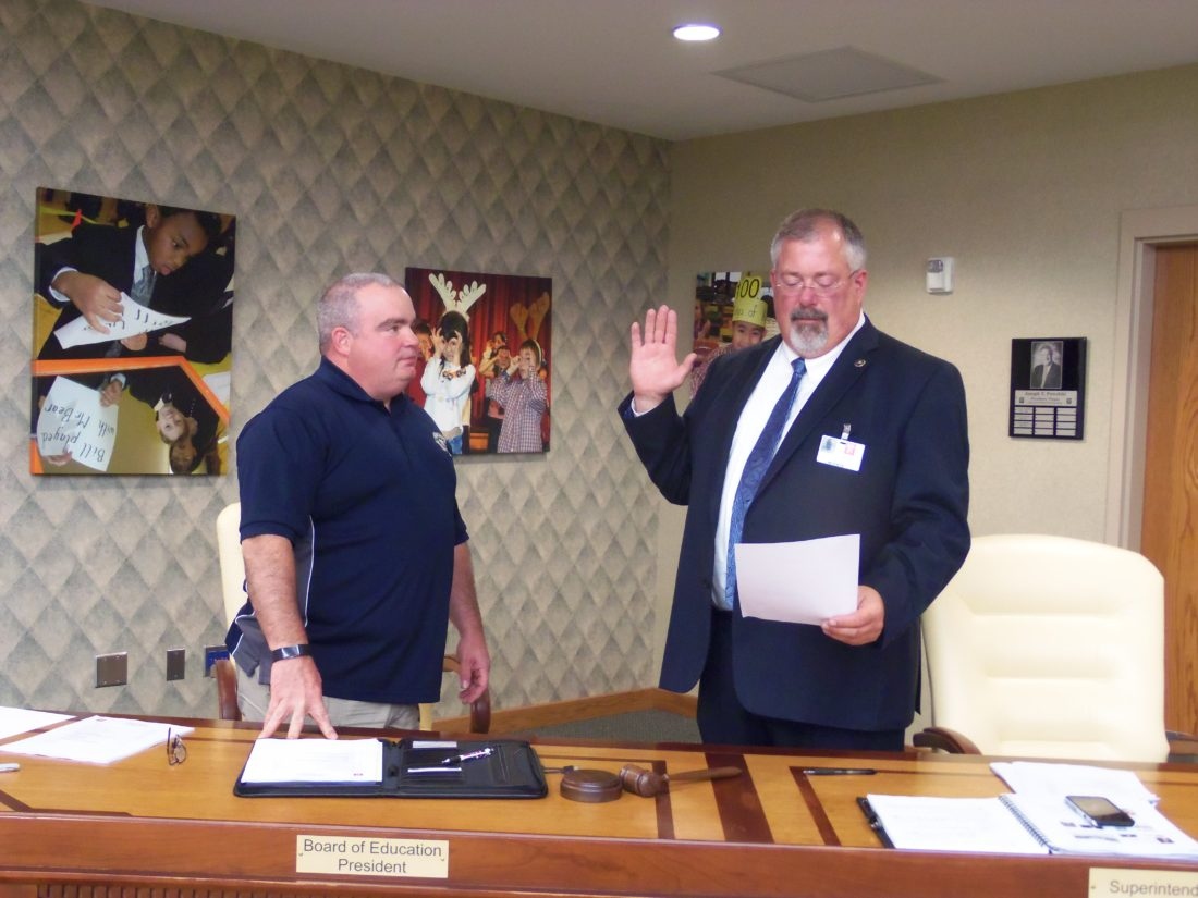 New Jamestown Public Schools District superintendent Bret Apthorpe took his oath at his first board of education meeting on Tuesday night. Pictured, from left, is Board President Paul Abbott and Apthorpe.  P-J photo by Katrina Fuller