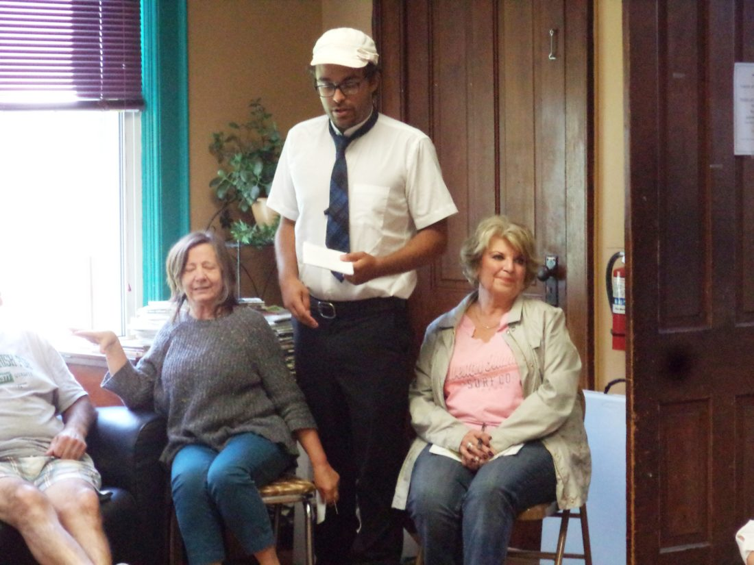 Zachary Mota, standing, rehearses his role as Lawrence Law, investigator of the Murder on the Petulant Express. Seated are Amy Neer, who plays Tonya Fennie; and Jan Culp, who plays Francien Cooper.