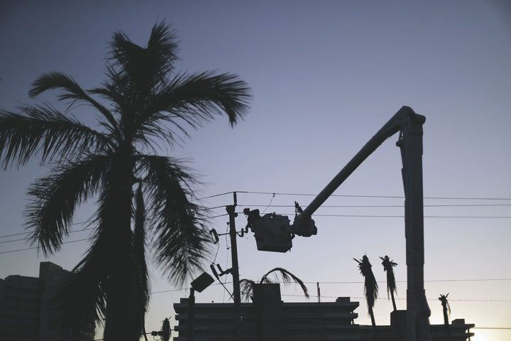 A worker is silhouetted against the setting sun as he works on a power line in the aftermath of Hurricane Irma in Marco Island, Fla., Tuesday.  AP photo