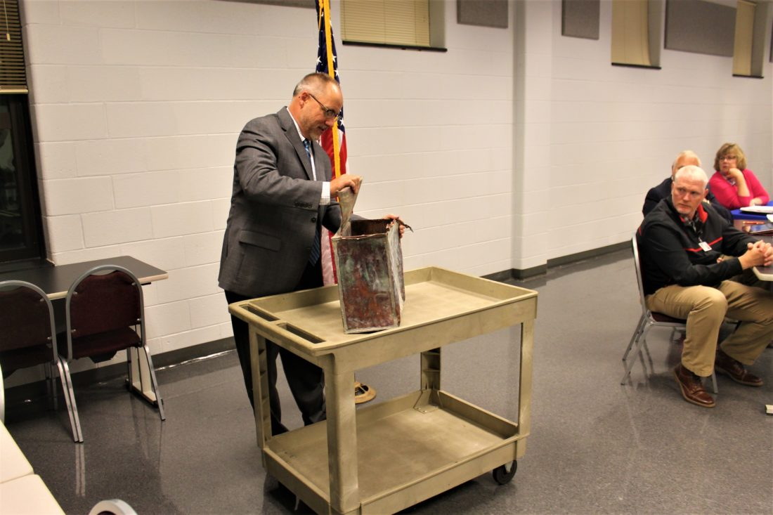 Superintendent Chuck Leichner, pictured, opened a time capsule from 1939 Monday during a meeting of the Cassadaga Valley Central School Board. The capsule was unearthed due to renovations taking place at the school. P-J photos by Jordan W. Patterson