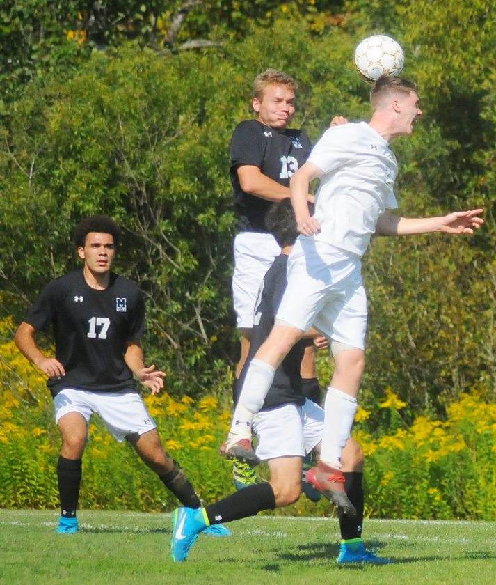 CC's Scott Crowe (2) leaps in the air to head a ball in front of Mercyhurst North East's Donald Brown during the men's game. P-J photo by Scott Kindberg