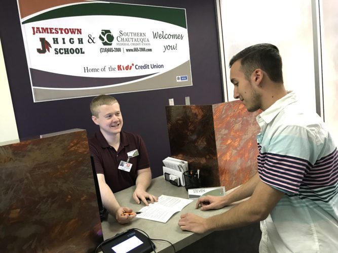Jamestown High School student, Geoffrey Tota, talks with Steven Olson with the Southern Chautauqua Federal Credit union who has partnered with JHS' Academy of Business, Management, Marketing & Technology to open a satellite branch in the JHS library to serve as an internship site for JHS students to experience real-world job opportunities in the banking industry.