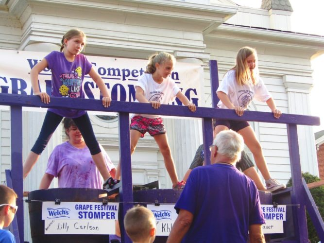 From left, Lilly Carlson, Khloe Karnes and Kimberly Bauer ready themselves during one of the heats at the Welch's grape stomping competition Friday, the first day of the 50th annual Festival of Grapes, in Silver Creek.  P-J photo by Greg Fox