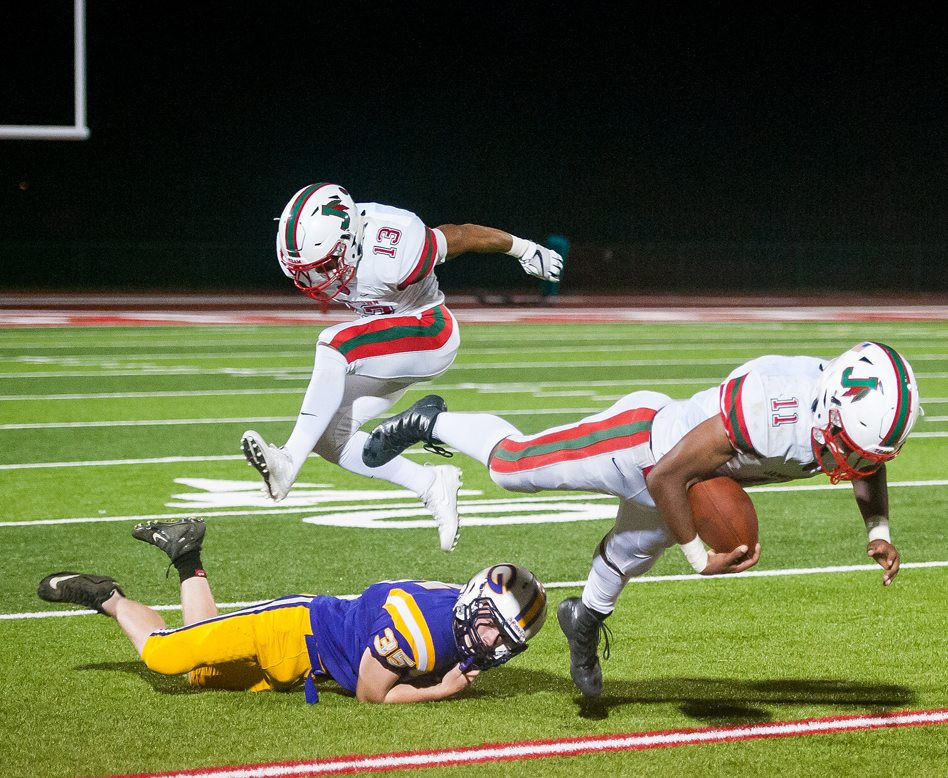 Jamestown's Savon VanSickle (11) is tripped up by Springville's Brendan Doktor (35) as the Red Raiders' Francisco Rodriguez (13) flies through the air during Friday night's non-league football game at Strider Field. P-J photo by Valory S. Isaacson
