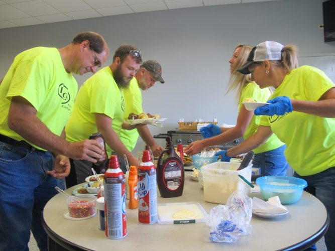 Employees make ice cream sundaes as part of their barbecue picnic on employee appreciation day. Photos by Remington Whitcomb