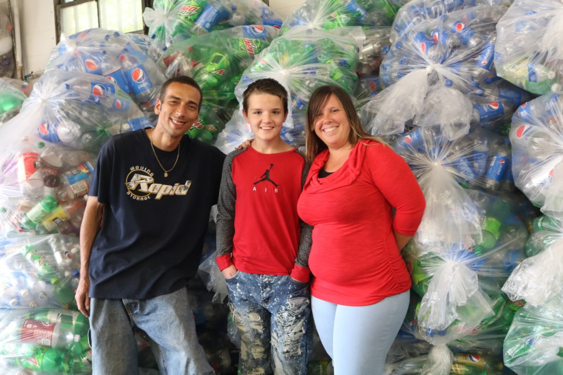 Christopher Decker and his mother, Amanda Martinelli, pose with Ryan Troutman at Bottles and Cans.