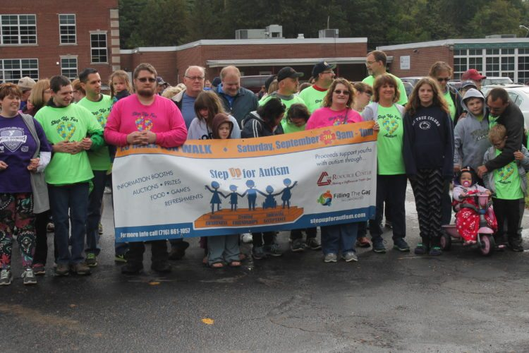 """Participants gathered Saturday outside holding a """"Step Up For Autism"""" banner before a 1.5-mile walk. Activities were held inside the Resource Center in Celoron to raise awareness. P-J photo by Jordan W. Patterson"""