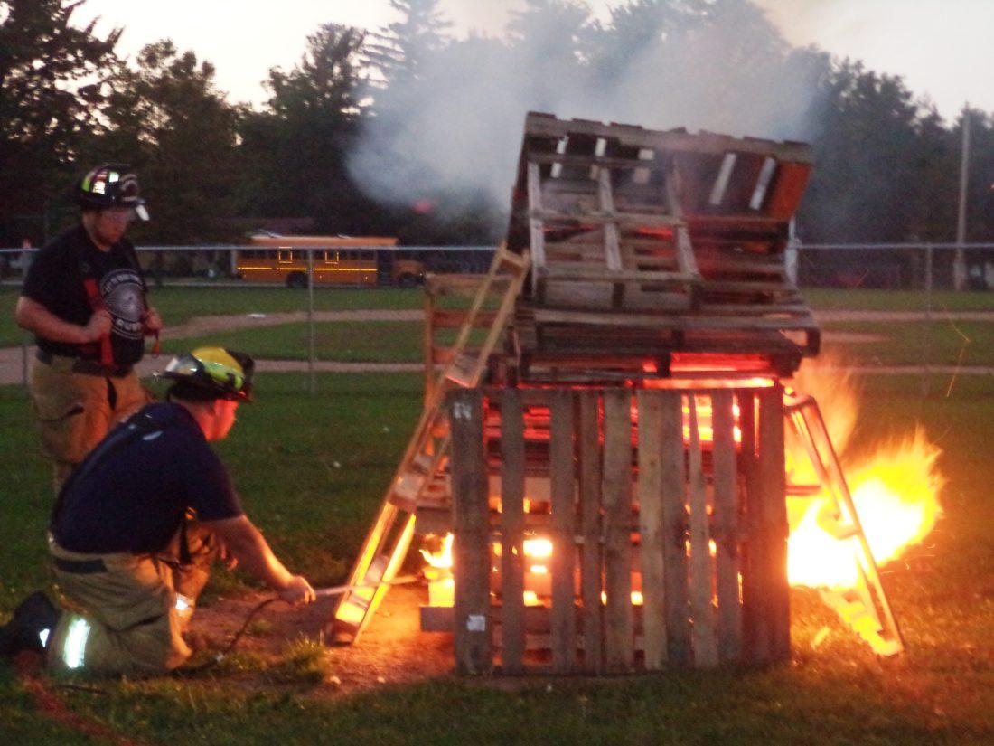 A member of the Westfield Fire Department lights a bonfire.