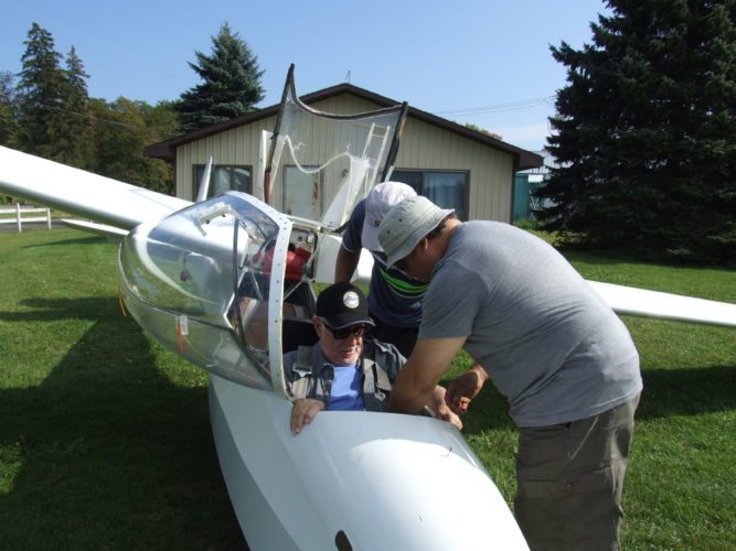 Dr. Galo Grijalva secures Fred Rowland before a glider ride at Aero Soaring Club located at Dart Field, Mayville, New York. Photos by Beverly Kehe-Rowland