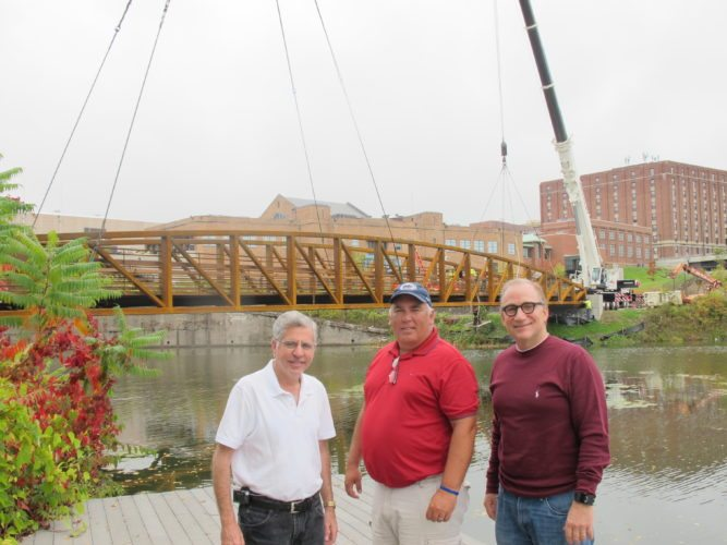 From left, Sam Teresi, Jamestown mayor, Jeff Lehman, city public works director, and Vince DeJoy, city development director, in front of the pedestrian bridge that was installed from the north shore of the Greater Jamestown Riverwalk to Panzarella Park Monday. The second pedestrian bridge is scheduled to be installed today along the Riverwalk below the Washington Street Bridge. P-J photos by Dennis Phillips