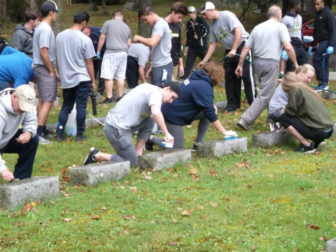 Jamestown Community College student athletes and coached cleaning veteran markers in Soldier's Circle at Lake View Cemetery Friday. More than 130 students and coaches cleaned more than 1,200  veteran markers during the volunteer service project.  Submitted photo