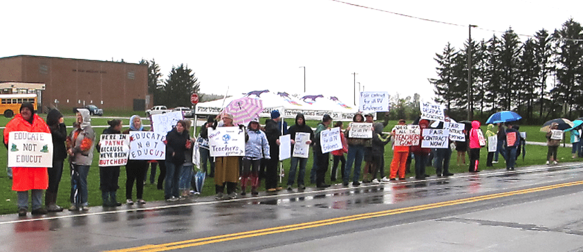 Pine Valley teachers and supporters stand next to Route 83 in front of the school building. Pine Valley has suffered an 18 percent turnover in teachers in the last four months.