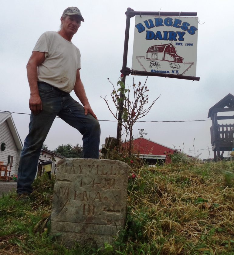 Dairy Farmer Benjamin Burgess stands near the mile-post stone he found in his field. Photos by David Prenatt