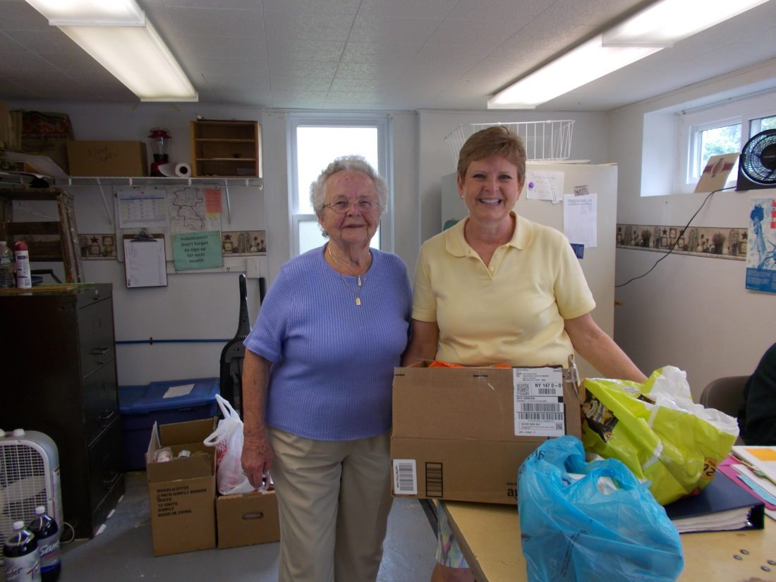 From left are Lou Wineman and Cass Wineman delivering food from the Chautauqua community food drive.