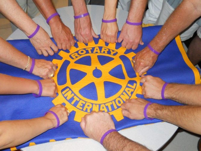 Rotarians join hands with their purple polio bracelets around the symbolic Rotary wheel.