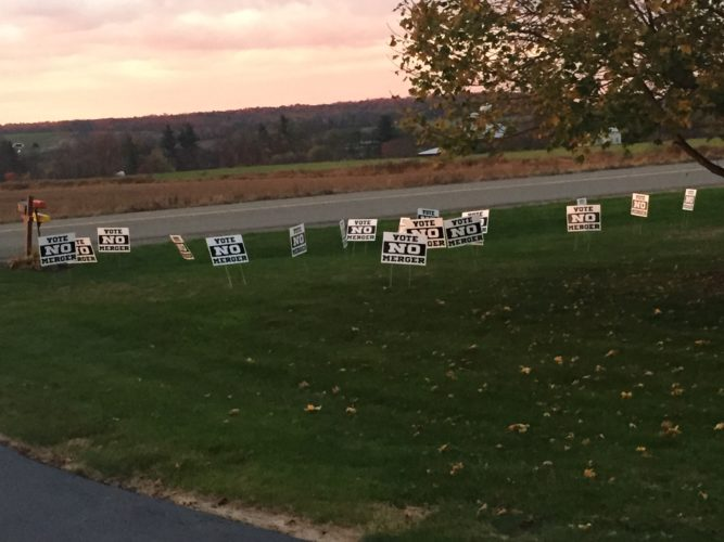 """""""Vote No Merger"""" signs were scattered through the yard of Clymer/Panama Superintendent Bert Lictus at some point early Saturday. Lictus asks that the community remain civil during merger talks between both schools."""