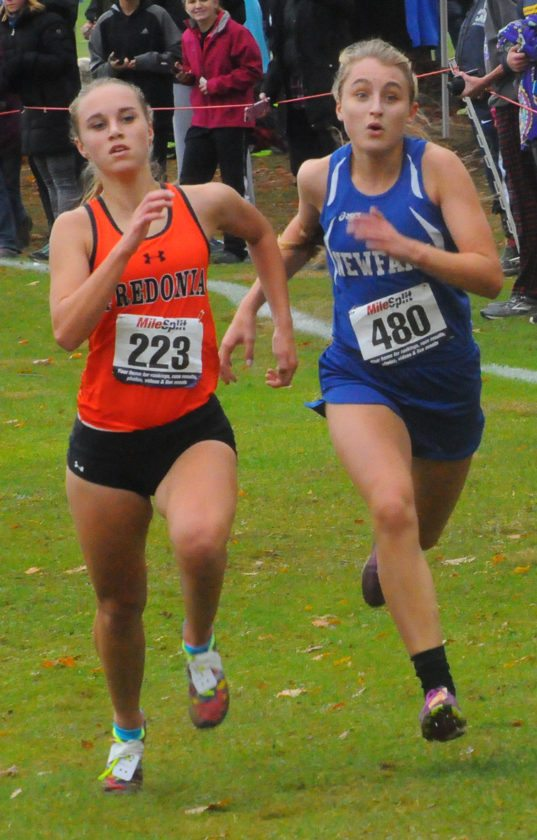 Fredonia's Emily Brown (223) holds off Newfane's Kimberly Goers in the Class C girls race. P-J photo by Scott Kindberg
