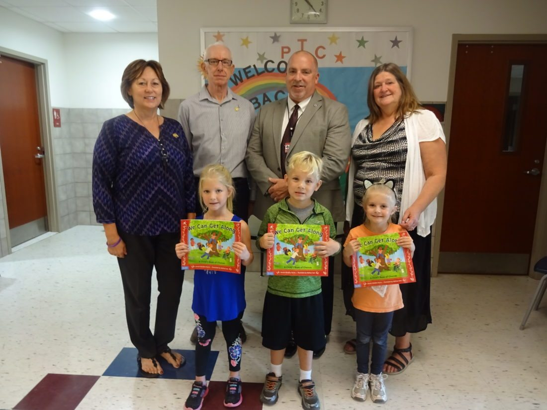 """On Oct. 4 Chautauqua Lake Central School kindergarten students (front, from left) Aubrey Olson, Ethan Hammond and Amelia Schieber were among the children who were given copies of the book titled """"We Can Get Along"""" written by Lauren Murphy Payne. In support of civility and literacy, all of this school district's kindergarten students received copies of the book from the Rotary Club of Westfield-Mayville. Also present were (back, from left) Club Public Relations Chair Sue Hammond; Club District Grants and Foundation Chair Jim Wakeman; CLCSD Superintendent and Rotarian Ben Spitzer; and CLCSD Elementary Principal Ella Ames. Photo By Wendy Westwood"""