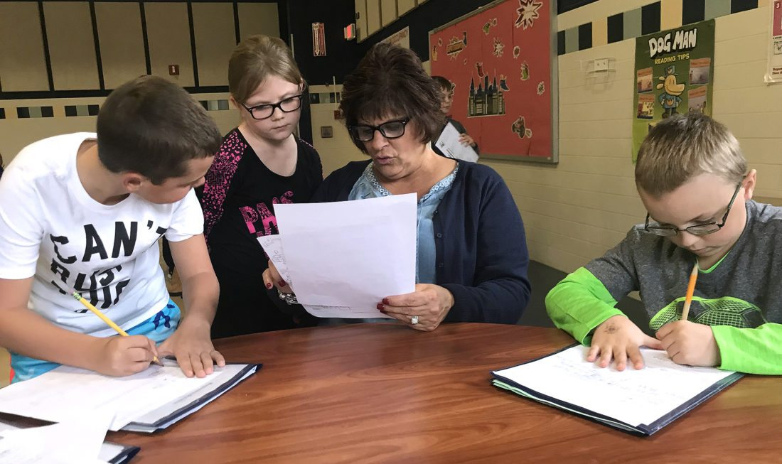 Lincoln Elementary School students, Carter Rizzuto, Kendall Hughes and Bryce Stone work on their homework during the after school program with Project LINC Director Cheryl Stone.