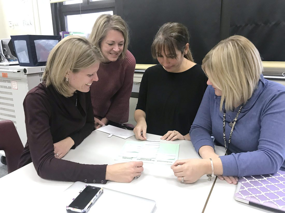 Lincoln Elementary School teachers, Cassie Stronz, Lynn Mayer and Heidi Maggio work as teams to place types of assessments into groups: pre-assessment, formative (ongoing) and summative during their Differentiated Learning Class as fellow teacher Rhonda Ricker looks on.