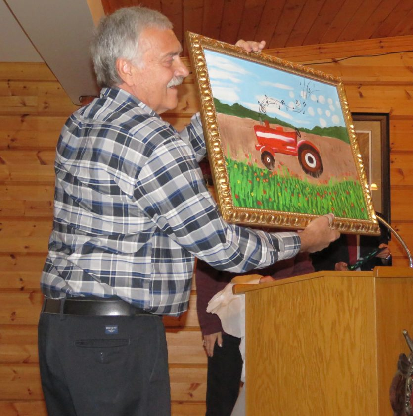 Volunteer of the Year Tom Rhodes shows off the painting made for him by artists with disabilities.