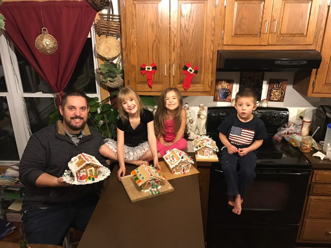 Ben Anderson gladly participated in gingerbread house construction with his nieces and nephew, from left: Bella Boehmer, Brynn Boehmer and Boomer Boehmer.