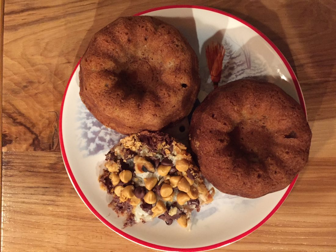 Banana Bread baked in minature bundt pans share a plate with Seven-Layer Bars.