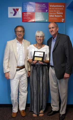 Rocky and Dixie Siegel pose for a picture with the Jamestown Area YMCA's CEO, Mark G. Eckendorf after receiving the YMCA's Partner with Youth Award, at the Jamestown YMCA's Downtown Branch.